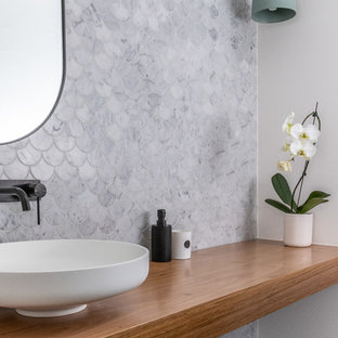 Photo of a contemporary cloakroom in Sydney with multi-coloured tiles, marble tiles, ceramic flooring, a vessel sink, wooden worktops and grey floors.
