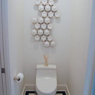 ニューヨークの小さいモダンスタイルのおしゃれなトイレ・洗面所 (一体型トイレ、ベージュのタイル、白い壁、セラミックタイルの床、格子天井、フラットパネル扉のキャビネット、茶色いキャビネット、アンダーカウンター洗面器、大理石の洗面台、ベージュの床、白い洗面カウンター、フローティング洗面台) の写真