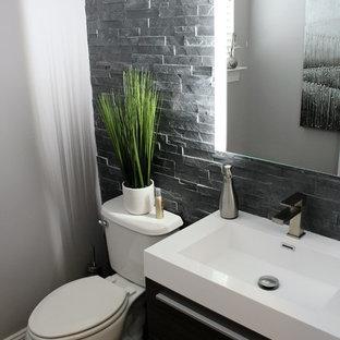 Ejemplo de aseo minimalista, de tamaño medio, con armarios con paneles lisos, puertas de armario de madera oscura, sanitario de una pieza, baldosas y/o azulejos grises, paredes grises, suelo de madera en tonos medios, lavabo suspendido y baldosas y/o azulejos de pizarra