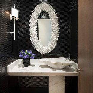 Réalisation d'un WC et toilettes design avec un carrelage noir, une vasque et un plan de toilette blanc.