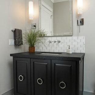 Стильный дизайн: туалет среднего размера в классическом стиле с фасадами с выступающей филенкой, черными фасадами, раздельным унитазом, серой плиткой, каменной плиткой, серыми стенами, полом из керамической плитки, столешницей из гранита и врезной раковиной - последний тренд
