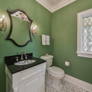 Diseño de aseo de estilo americano, pequeño, con armarios con paneles con relieve, puertas de armario blancas, sanitario de dos piezas, paredes verdes, suelo de mármol, lavabo bajoencimera, encimera de granito y encimeras negras