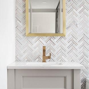Идея дизайна: маленький туалет в стиле современная классика с серыми фасадами, унитазом-моноблоком, плиткой мозаикой, мраморным полом, врезной раковиной, столешницей из искусственного кварца и фасадами с утопленной филенкой