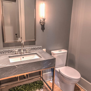 Powder room - small contemporary light wood floor and beige floor powder room idea in Atlanta with a one-piece toilet, gray walls and a console sink