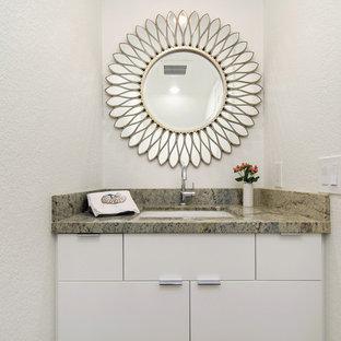 Пример оригинального дизайна: маленький туалет в стиле модернизм с плоскими фасадами, белыми фасадами, белыми стенами, паркетным полом среднего тона, врезной раковиной, столешницей из гранита, коричневым полом и зеленой столешницей