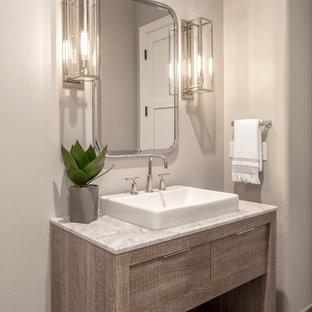 Свежая идея для дизайна: туалет среднего размера в стиле кантри с плоскими фасадами, светлыми деревянными фасадами, унитазом-моноблоком, серой плиткой, керамической плиткой, серыми стенами, полом из цементной плитки, настольной раковиной, мраморной столешницей, серым полом и серой столешницей - отличное фото интерьера