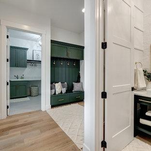 На фото: туалеты среднего размера в стиле кантри с фасадами островного типа, зелеными фасадами, раздельным унитазом, белыми стенами, светлым паркетным полом, настольной раковиной, столешницей из искусственного камня, коричневым полом и белой столешницей