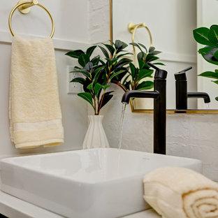 Aménagement d'un WC et toilettes campagne de taille moyenne avec un placard en trompe-l'oeil, des portes de placards vertess, un WC séparé, un mur blanc, un sol en bois clair, une vasque, un plan de toilette en surface solide, un sol marron et un plan de toilette blanc.