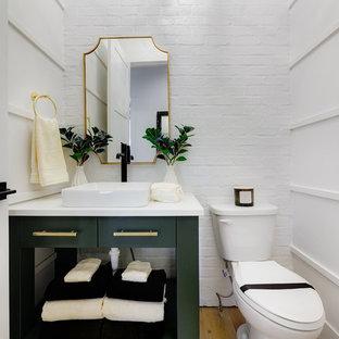 Inredning av ett lantligt mellanstort vit vitt toalett, med möbel-liknande, gröna skåp, en toalettstol med separat cisternkåpa, vita väggar, ljust trägolv, ett fristående handfat, bänkskiva i akrylsten och brunt golv