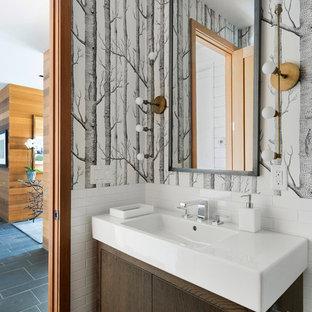Свежая идея для дизайна: туалет в стиле современная классика с плоскими фасадами, темными деревянными фасадами, белой плиткой, плиткой кабанчик, серыми стенами, монолитной раковиной и черным полом - отличное фото интерьера