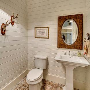 Неиссякаемый источник вдохновения для домашнего уюта: туалет в стиле кантри с раковиной с пьедесталом, белыми стенами и кирпичным полом