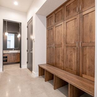 Exemple d'un grand WC et toilettes nature avec un placard à porte plane, des portes de placard en bois brun, un WC séparé, un carrelage noir, des dalles de pierre, un mur noir, béton au sol, une vasque, un plan de toilette en quartz, un sol gris et un plan de toilette beige.