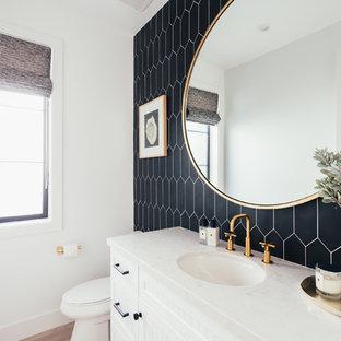 Exemple d'un WC et toilettes nature de taille moyenne avec un placard à porte shaker, des portes de placard blanches, un WC à poser, un mur noir, un sol en bois clair, un lavabo encastré, un plan de toilette en quartz modifié et un plan de toilette blanc.