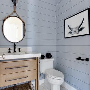 Modelo de aseo de estilo de casa de campo con armarios tipo mueble, puertas de armario de madera clara, sanitario de dos piezas, paredes grises, lavabo bajoencimera, suelo blanco, encimeras blancas y encimera de cuarcita