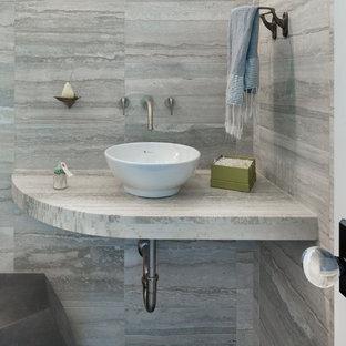 Idée de décoration pour un petit WC et toilettes design avec une vasque, un plan de toilette en calcaire, un carrelage gris et du carrelage en pierre calcaire.