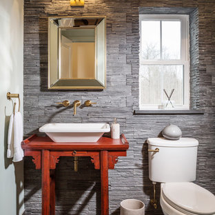 Powder room - small transitional gray tile ceramic floor powder room idea in Milwaukee with a vessel sink, furniture-like cabinets, red cabinets, a two-piece toilet, gray walls, wood countertops and red countertops