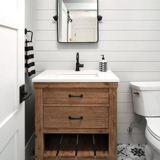 Modelo de aseo campestre con armarios tipo mueble, puertas de armario de madera oscura, paredes grises, suelo de baldosas de porcelana, lavabo bajoencimera, encimera de cuarzo compacto y encimeras blancas