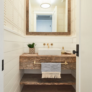 Beach style medium tone wood floor and brown floor powder room photo in Los Angeles with beige walls, a vessel sink, wood countertops and brown countertops
