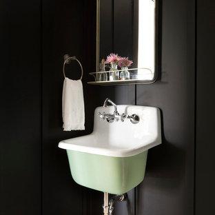 Imagen de aseo campestre con paredes negras y lavabo suspendido