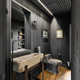 Diseño de aseo panelado, campestre, panelado, con puertas de armario grises, sanitario de una pieza, encimera de piedra caliza, paredes negras, suelo de madera en tonos medios, lavabo tipo consola, suelo marrón y panelado