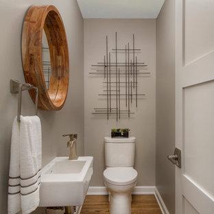 Inspiration pour un petit WC et toilettes traditionnel avec un lavabo suspendu, un mur gris, un sol en bois brun et un WC séparé.