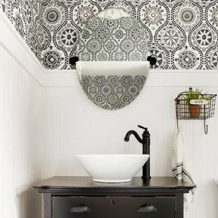 Идея дизайна: туалет среднего размера в стиле модернизм с фасадами островного типа, искусственно-состаренными фасадами, унитазом-моноблоком, желтой плиткой, синими стенами, настольной раковиной, столешницей из дерева и коричневой столешницей