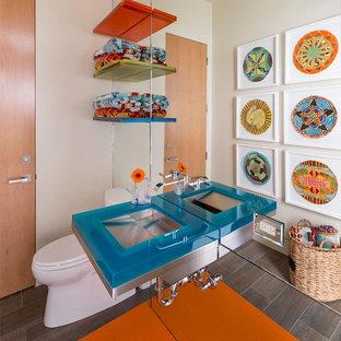 Imagen de aseo vintage, de tamaño medio, con armarios abiertos, sanitario de una pieza, paredes beige, suelo de baldosas de porcelana, lavabo integrado, encimera de vidrio y encimeras azules