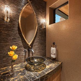Exemple d'un grand WC et toilettes tendance avec un placard en trompe-l'oeil, des portes de placard en bois clair, un carrelage beige, un carrelage de pierre, un mur beige, un sol en marbre, un lavabo encastré et un plan de toilette en granite.