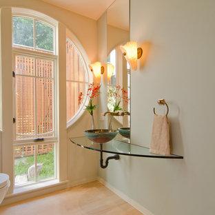 Стильный дизайн: туалет среднего размера в современном стиле с настольной раковиной, синими стенами, светлым паркетным полом, стеклянной столешницей и бежевым полом - последний тренд