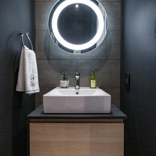 Пример оригинального дизайна: маленький туалет в стиле модернизм с плоскими фасадами, светлыми деревянными фасадами, унитазом-моноблоком, серой плиткой, керамогранитной плиткой, черными стенами, полом из керамогранита, настольной раковиной, столешницей из ламината, серым полом и черной столешницей