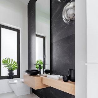 Immagine di un bagno di servizio moderno di medie dimensioni con WC monopezzo, piastrelle nere, pareti bianche, pavimento in marmo, lavabo a bacinella, top in legno, pavimento bianco e top beige