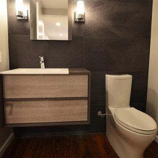 Idee per un piccolo bagno di servizio minimalista con ante lisce, ante grigie, WC a due pezzi, piastrelle in gres porcellanato, pareti nere, lavabo integrato, top in quarzo composito e piastrelle grigie