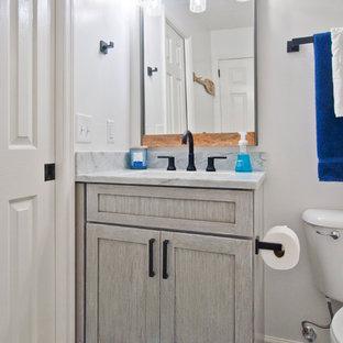 Immagine di un piccolo bagno di servizio tradizionale con ante in stile shaker, ante grigie, WC a due pezzi, piastrelle bianche, piastrelle di marmo, pareti grigie, pavimento in pietra calcarea, lavabo sottopiano, top in marmo, pavimento grigio e top bianco
