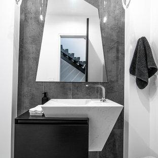 Свежая идея для дизайна: туалет в современном стиле с плоскими фасадами, черными фасадами, серыми стенами, серым полом и черной столешницей - отличное фото интерьера