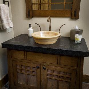 他の地域の中サイズのラスティックスタイルのおしゃれなトイレ・洗面所 (濃色木目調キャビネット、白い壁、ベッセル式洗面器、ソープストーンの洗面台、マルチカラーの床、黒い洗面カウンター) の写真