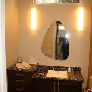 エドモントンの小さいコンテンポラリースタイルのおしゃれなトイレ・洗面所 (シェーカースタイル扉のキャビネット、濃色木目調キャビネット、分離型トイレ、ベージュの壁、磁器タイルの床、オーバーカウンターシンク、テラゾーの洗面台) の写真