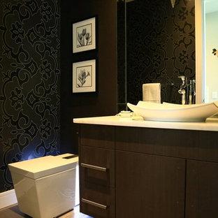 На фото: с высоким бюджетом туалеты среднего размера в стиле модернизм с настольной раковиной, плоскими фасадами, мраморной столешницей, раздельным унитазом, серой плиткой, керамогранитной плиткой, черными стенами, полом из керамогранита и коричневыми фасадами