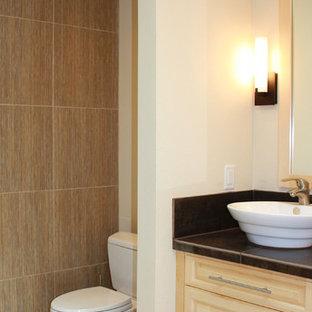 Foto di un bagno di servizio minimalista di medie dimensioni con ante con bugna sagomata, ante in legno chiaro, WC a due pezzi, piastrelle nere, lastra di pietra, pareti beige, pavimento con piastrelle in ceramica, lavabo a bacinella, top in superficie solida e pavimento beige