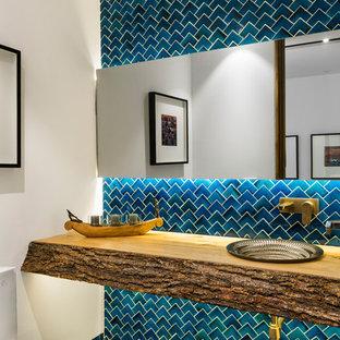 Cette image montre un WC et toilettes design avec un carrelage bleu, un mur blanc, un lavabo posé, un plan de toilette en bois, un sol bleu et un plan de toilette marron.