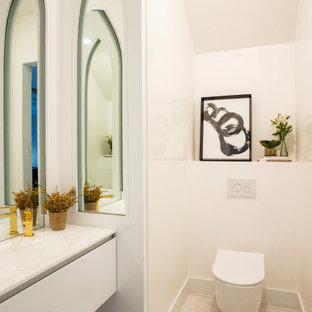 マイアミの広いコンテンポラリースタイルのおしゃれなトイレ・洗面所 (フラットパネル扉のキャビネット、白いキャビネット、白いタイル、白い壁、大理石の床、ガラスの洗面台、白い床、白い洗面カウンター、壁掛け式トイレ、一体型シンク、三角天井) の写真