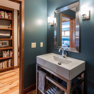 Idee per un piccolo bagno di servizio minimal con nessun'anta, pavimento in legno massello medio, pareti blu e lavabo integrato