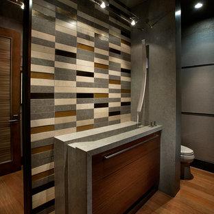 Пример оригинального дизайна: туалет в современном стиле с монолитной раковиной, плоскими фасадами, темными деревянными фасадами, разноцветной плиткой, плиткой из известняка, серыми стенами, паркетным полом среднего тона, коричневым полом и серой столешницей