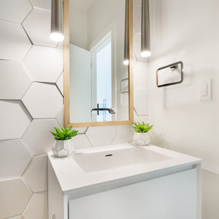 Design ideas for a small modern cloakroom in Vancouver with open cabinets, white cabinets, a one-piece toilet, white tiles, porcelain tiles, white walls, light hardwood flooring, an integrated sink, solid surface worktops, yellow floors and white worktops.