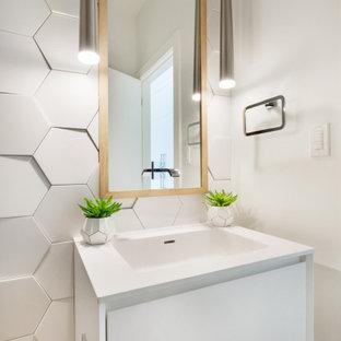 Aménagement d'un petit WC et toilettes moderne avec un placard sans porte, des portes de placard blanches, un WC à poser, un carrelage blanc, des carreaux de porcelaine, un mur blanc, un sol en bois clair, un lavabo intégré, un plan de toilette en surface solide, un sol jaune et un plan de toilette blanc.
