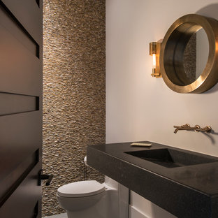Example of a small trendy beige tile and stone tile porcelain floor powder room design in Miami with white walls, a one-piece toilet, concrete countertops, an integrated sink and black countertops