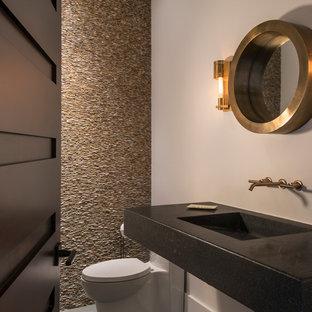 Inspiration pour un petit WC et toilettes design avec un mur blanc, un sol en carrelage de porcelaine, un WC à poser, un carrelage beige, un carrelage de pierre, un plan de toilette en béton, un lavabo intégré et un plan de toilette noir.