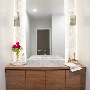 Idée de décoration pour un WC et toilettes design de taille moyenne avec un placard à porte plane, des portes de placard en bois brun, un carrelage blanc, un carrelage de pierre, un mur gris, un sol en carrelage de porcelaine, une vasque, un plan de toilette en bois et un plan de toilette marron.