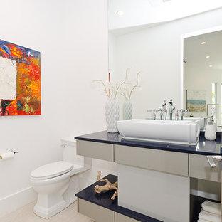 На фото: большие туалеты в стиле модернизм с плоскими фасадами, белыми фасадами, раздельным унитазом, белыми стенами, светлым паркетным полом, настольной раковиной, столешницей из искусственного камня, бежевым полом и синей столешницей