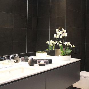Ispirazione per un bagno di servizio moderno di medie dimensioni con ante lisce, ante grigie, WC sospeso, piastrelle grigie, piastrelle in pietra, pareti grigie e lavabo sottopiano