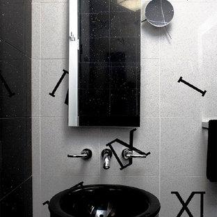 На фото: огромный туалет в стиле модернизм с унитазом-моноблоком, черно-белой плиткой, каменной плиткой, белыми стенами и раковиной с пьедесталом с